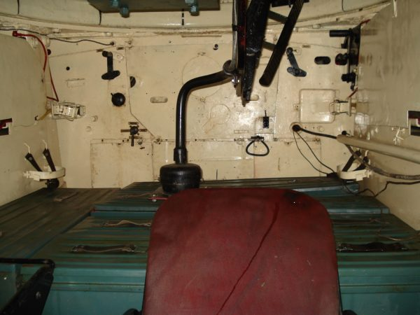 Interior of a T-34-85 viewed from the driver's hatch, showing the ammunition boxes on which the loader had to stand in the absence of a turret basket. In the foreground is the driver's seat. Levers for radiator flaps can be seen on the firewall. Balcer – CC BY 2.5