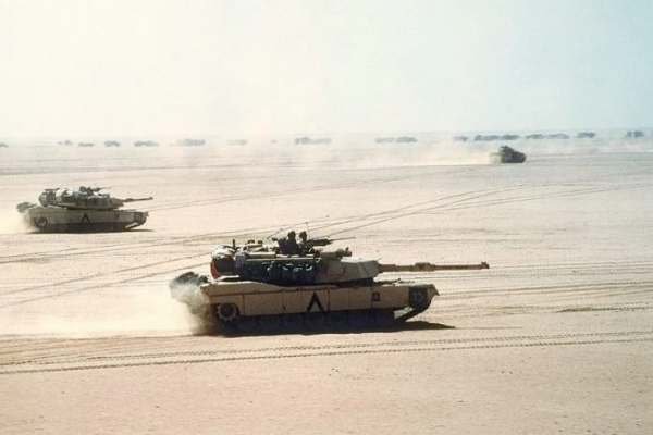Abrams tanks move out on a mission during Desert Storm in 1991. A Bradley IFV and logistics convoy can be seen in the background.