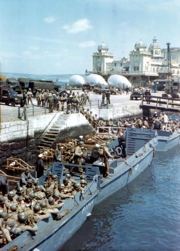 US Army soldiers boarding landing craft at Weymouth, Dorset, England, United Kingdom, while preparing for the Normandy operation, 1 May 1944; note barrage balloons aloft and on the ground.