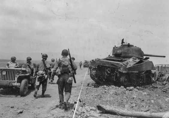 GIs walk past a knocked out M4 Sherman at the Anzio Front