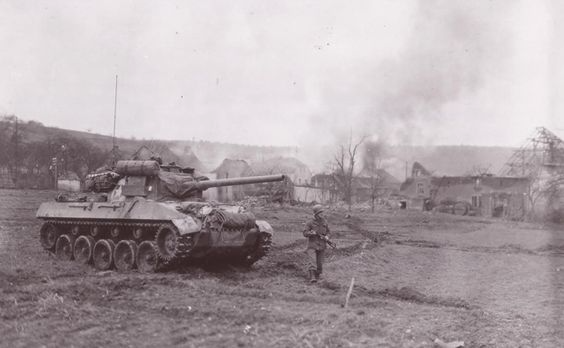 """Hellcat with walking GI in front of a burning town. This photo was identified by its driver Sgt. Harry E. Traynor of the 704th TD Bn. The soldier in the front is Cpt. Marion Taake, The TD was named """"Blondie"""" and it was later destroyed on February 9, 1945 by two German Panther tanks in the Bannholz Woods area of Germany."""