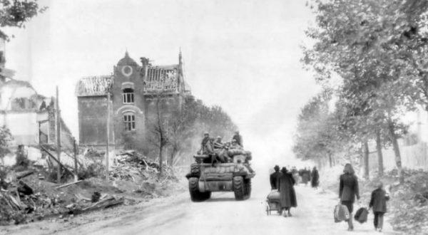 Civilians leave for Allied lines as M10 enters Aachen, 1944
