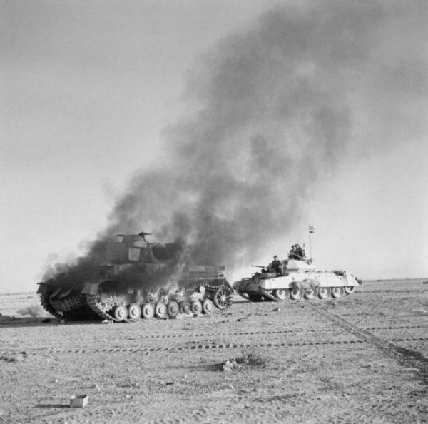 A British Crusader tank passing a burning German Panzer IV during Operation Crusader, late 1941.