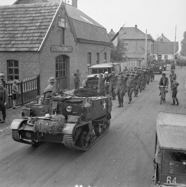 A British Army Universal Carrier leads some German prisoners-of-war into a European town.