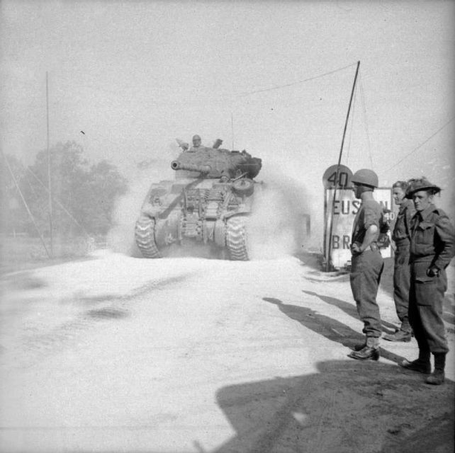A Sherman Firefly crosses 'Euston Bridge' over the Orne as it moves up to the start line for Operation Goodwood, 18 July 1944